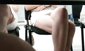 Les culottes d'une fille filmées sous la table