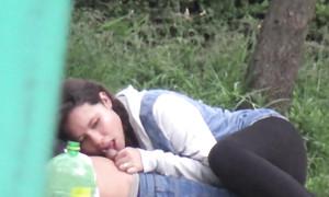 Une étudiante lèche la bite en cachette dans un parc public