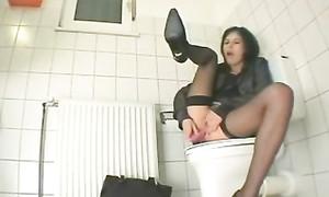 Secrétaire se gode le cul et la chatte dans les toilettes